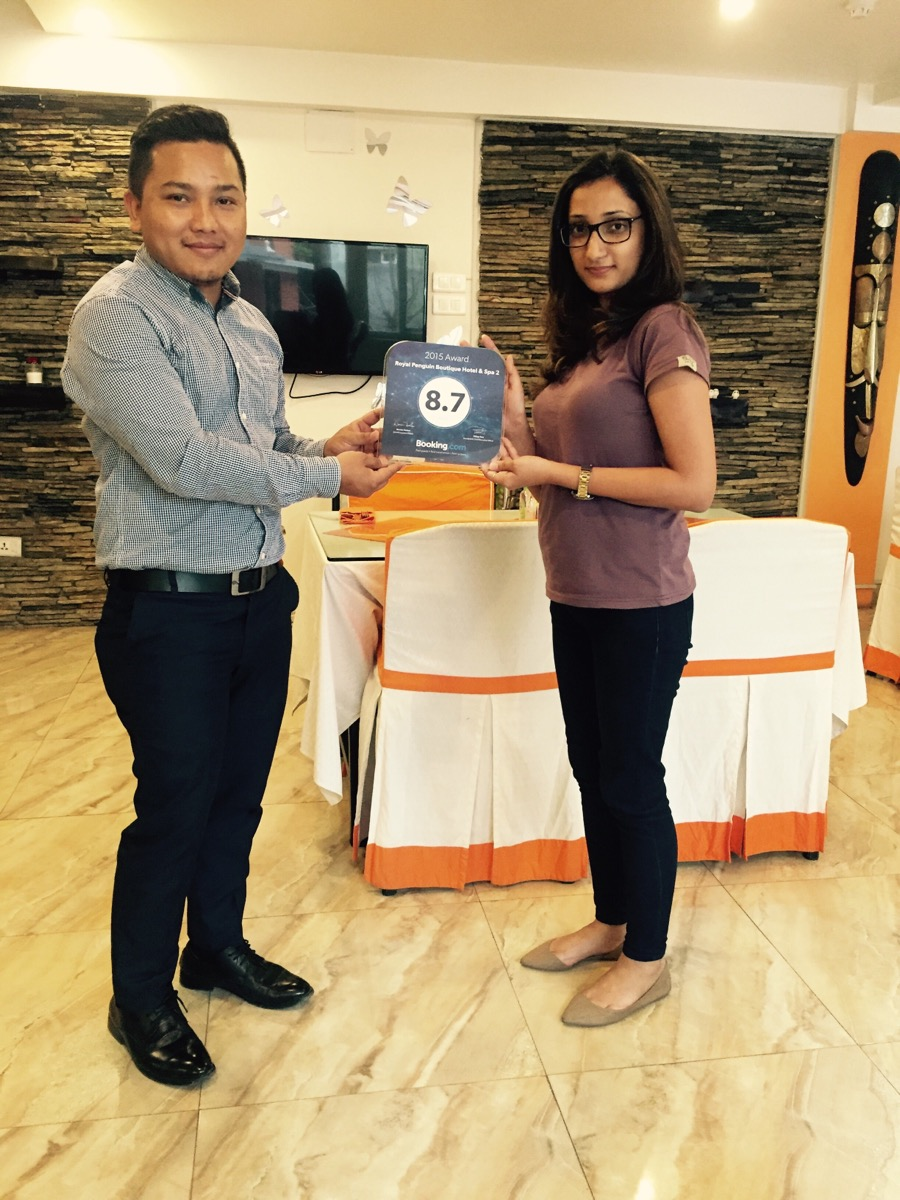 Mr Bishal Tamang Residence Manager  receiving award of Booking.com for Royal Penguin Boutique Hotel & Spa 2 from Ms Aanchal Pareek from Booking.com